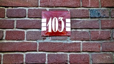 photo focused on plate with the number used to refer to the house made of brick