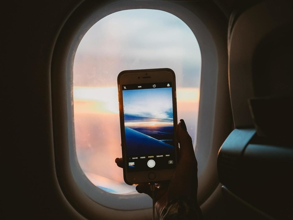 person holding smartphone inside airplane taking picture of the outside